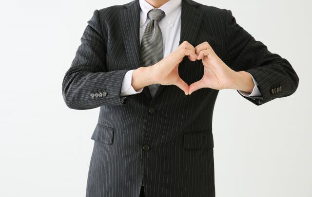 胸の前でハートを作るスーツの男性