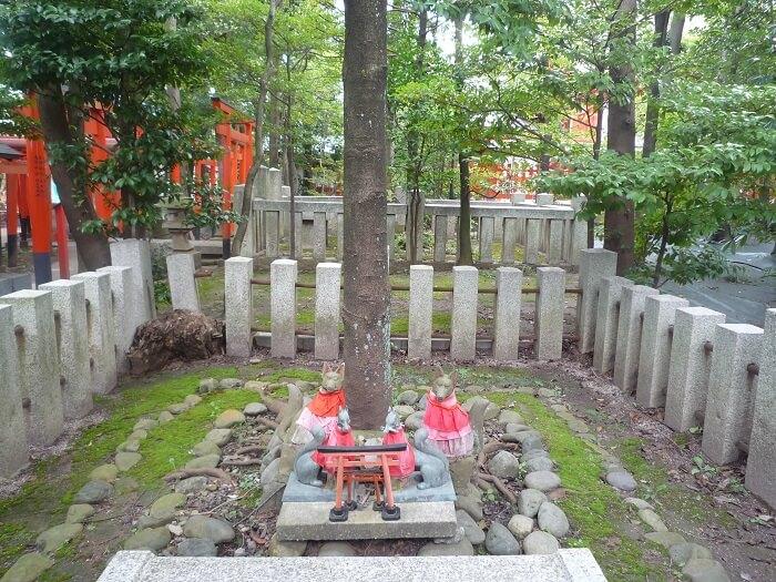 狐の石像の中心にある木