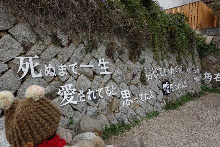 クマのぬいぐるみと壁の文字