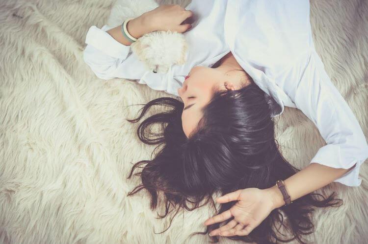 犬を抱きながら横になる女性