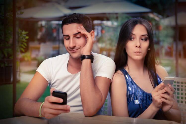 スマホを見る男性と覗く女性