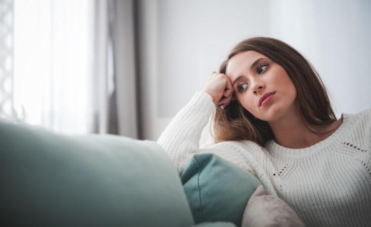 ソファの上で悩む女性